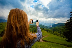 woman taking photo of landscape