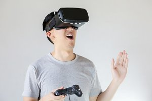 Asian man wearing VR goggle and immersing himself in VR gaming in white isolated