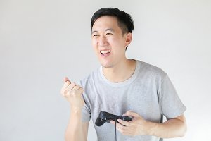 Young Asian man playing video games - in white isolated background