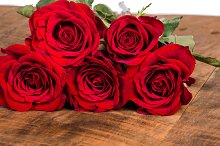 Red roses laying on a wooden table