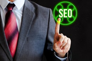 Businessman pressing SEO icon in the air with one finger - search engine optimization, internet business concept