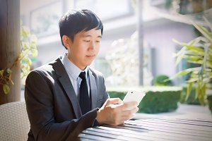 Young Asian businessman using phone in the outdoor scene