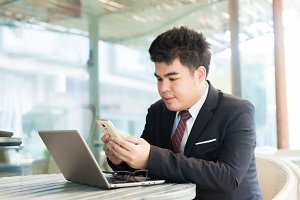 Young Asian businessman playing his phone and laptop in the outdoor scene