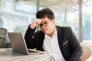 Young Asian businessman facing a problem and thinking of solution