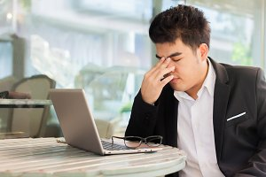 Young Asian businessman suffering from tired eyes after long hours of using laptop.