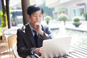 Young Asian casual businessman thinking while working in outdoor scene