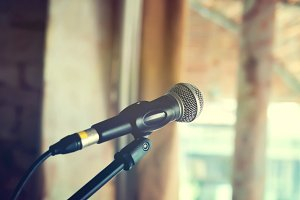 Black vintage mic on indoor stage -in vintage tone (selective focus)