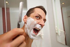 Man is holding a straight razor.
