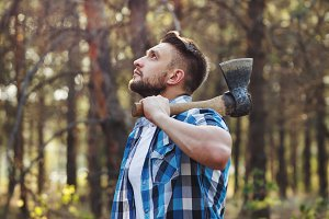 Lumberjack with an ax chooses tree.