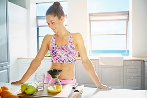 Shapely healthy young woman making fresh juice