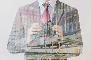Double Exposure of Businessman in suit with skyscraper on the background
