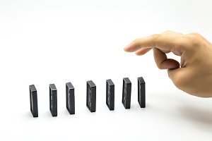 Hand pushing dominoes isolated on white background - domino effect, business risk concept