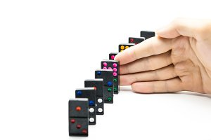 Businessman hand stopping domino effect on isolated white background with copy space - business solution, strategy and successful intervention concept