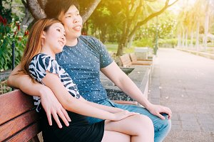 Asian couple sitting on the bench in the park together