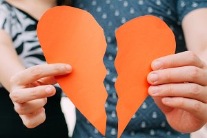 Couple holding a half heart shape breaking apart - divorce, split concept