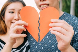 Couple trying to connect two pieces of paper heart - relationship, in love concept