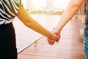 Couple in love holding hands with each other on the pier