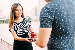 Male giving a gift box to his female partner. Happy relationship in outdoor scene. Love and relationship concept