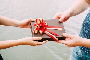 Couple giving a gift box to each other. Happy relationship in outdoor scene. Love and relationship concept