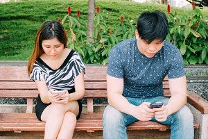 Young couple playing with smartphones and ignoring each other