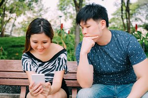 Jealous boyfriend peeking and spying his girlfriend mobile phone while she is reading a message