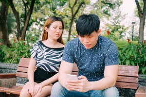 Jealous girlfriend peeking and spying her boyfriend mobile phone while he is reading a message