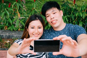 Asian couple taking a selfie photo in outdoor park scene - love and relationship concept