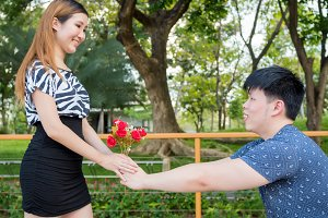 Asian man kneels down giving his girlfriend a bunch of roses