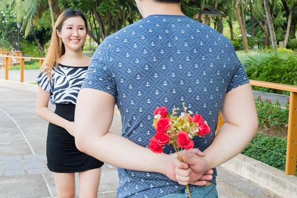 Young man hiding roses from his bac…