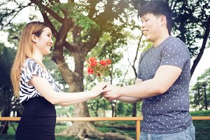 Asian couple handing a bunch of roses in the public park - in vintage tone