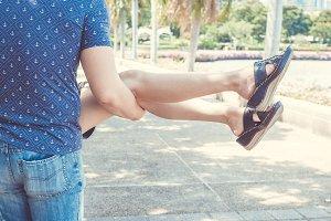 Happy boyfriend carrying girlfriend in the outdoor public park