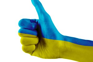 Ukraine flag painted hand showing thumbs up sign on isolated white background with clipping path