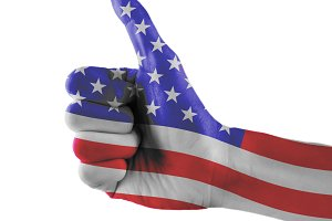 United States or USA or American flag painted hand showing thumbs up sign on isolated white background with clipping path