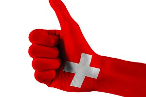 Switzerland or Swiss flag painted hand showing thumbs up sign on isolated white background with clipping path
