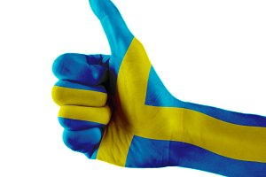 Sweden flag painted hand showing thumbs up sign on isolated white background with clipping path