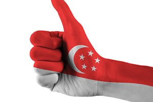 Singapore flag painted hand showing thumbs up sign on isolated white background with clipping path