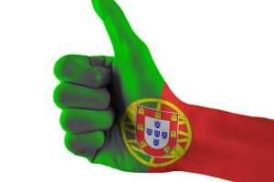 Portugal flag painted hand showing thumbs up sign on isolated white background with clipping path