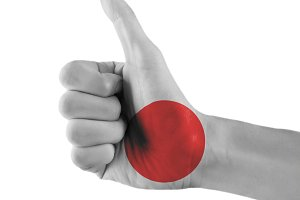 Japan flag painted hand showing thumbs up sign on isolated white background with clipping path