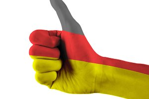 Germany flag painted hand showing thumbs up sign on isolated white background with clipping path