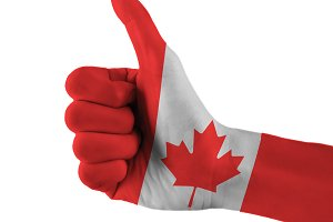 Canada flag painted hand showing thumbs up sign on isolated white background with clipping path