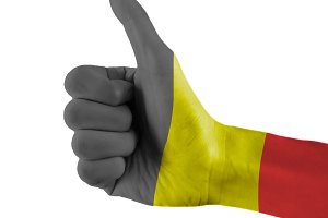 Belgium flag painted hand showing thumbs up sign on isolated white background with clipping path