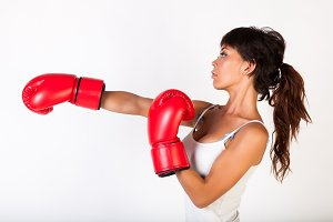Young beautiful woman punching while wearing boxing gloves on white isolated background - fitness and power concept