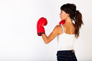 Young beautiful woman guarding while wearing boxing gloves on white isolated background - fitness and power concept