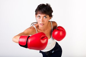 Young beautiful woman punching towards camera wearing boxing gloves on isolated white background - fitness and power concept