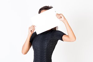 A beautiful woman holds out a blank paper and hiding her face isolated on white background