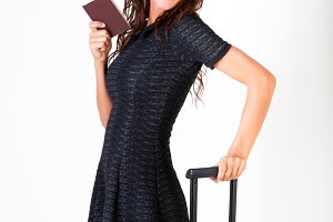 Attractive tourist woman showing passport with suitcase on isolated white background - travel and vacation concept