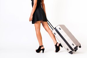 Attractive tourist woman with suitcase on isolated white background - travel and vacation concept