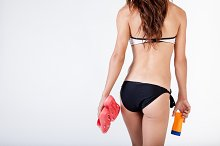 Back of walking woman in bikini holding sandals and sun screen lotion in white isolated