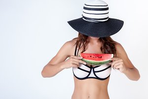 Woman in bikini with summer hat and watermalon in white isolated