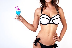Young woman in bikini holding summer beverage in white isolated background